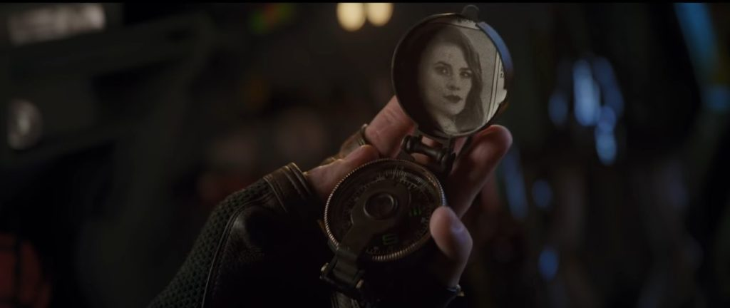 Captain America holding a locket with a photo of a young Peggy Carter in his hands