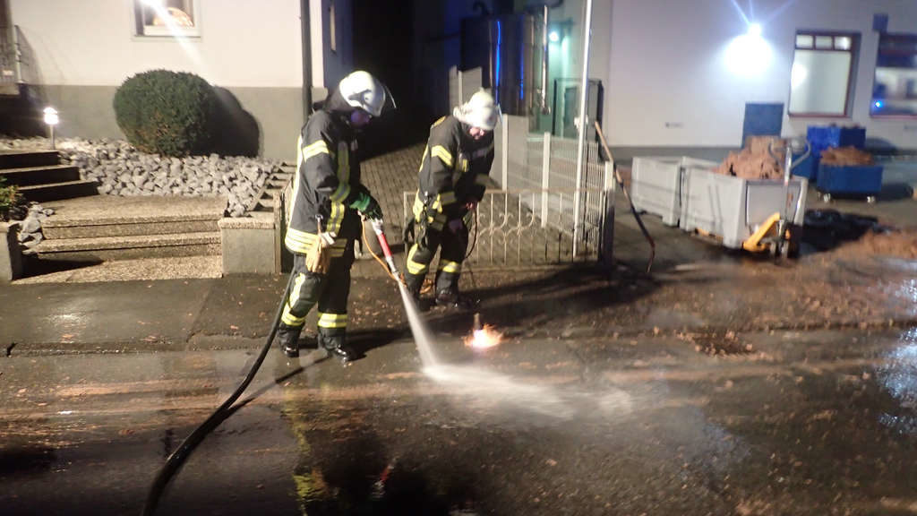 Firefighers use fire torches and hot water to try to melt out the chocolate and wash the chocolate away.